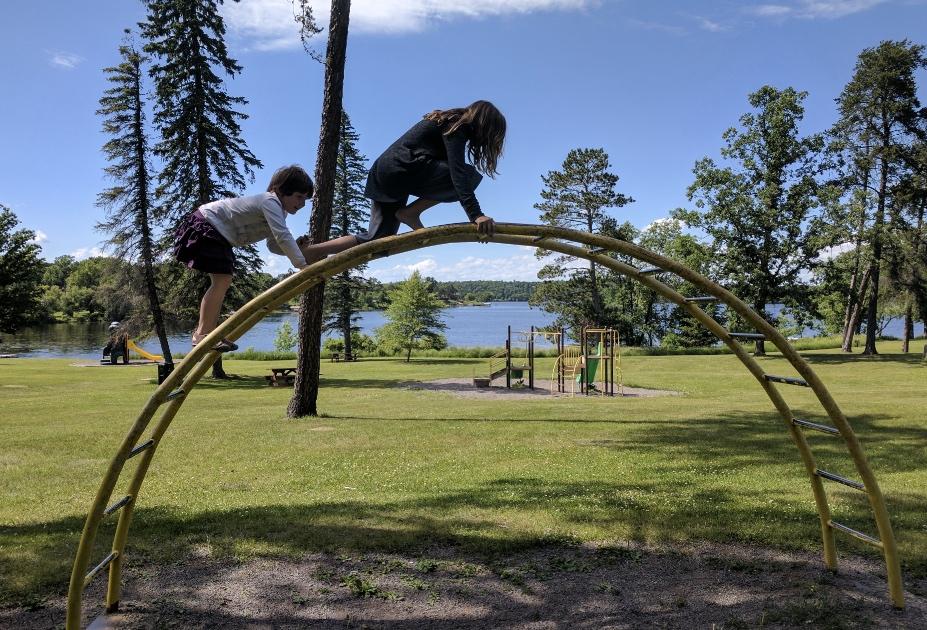 Two girls climbing a jungle gym at Lum Park Brainerd Minnesota
