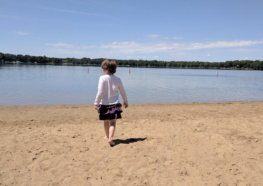 A girl walks along Whipple Beach Baxter Minnesta